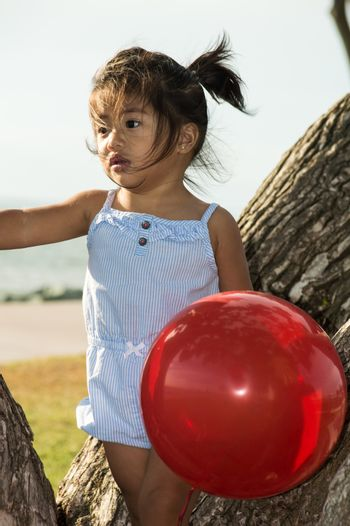 Little Girl in a Tree with Balloon