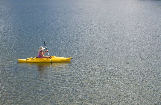 Woman Kayaking on Beautiful Peaceful Mountain Lake.
