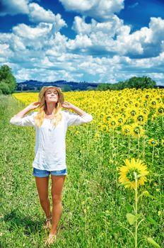 Joyful girl in sunflowers field