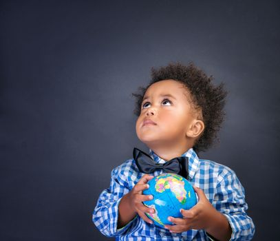 Little schoolboy with globe in hands