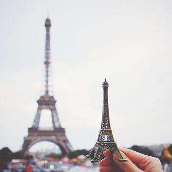 Hand holding eiffel tower model in paris, retro filter effect