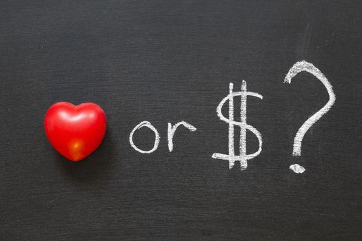 love or dollars? phrase handwritten on school blackboard