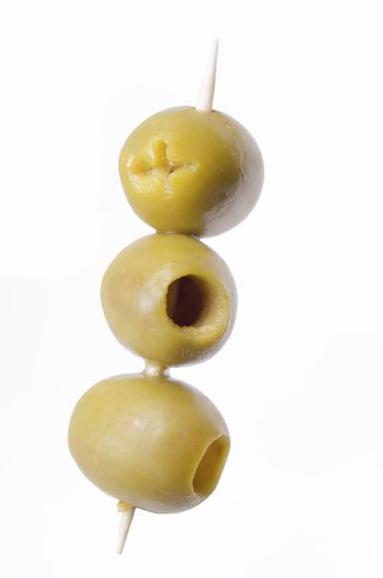 three pitted green olives on wooden stick