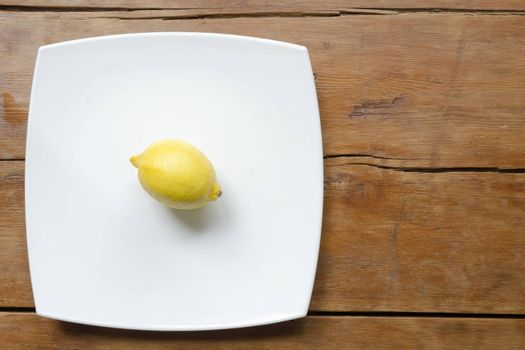 lemon on white ceramic square dish on the vintage wooden table