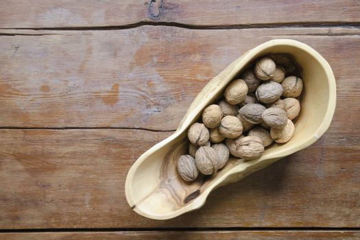 scenic wooden bowl full of walnuts on the vintage wooden table
