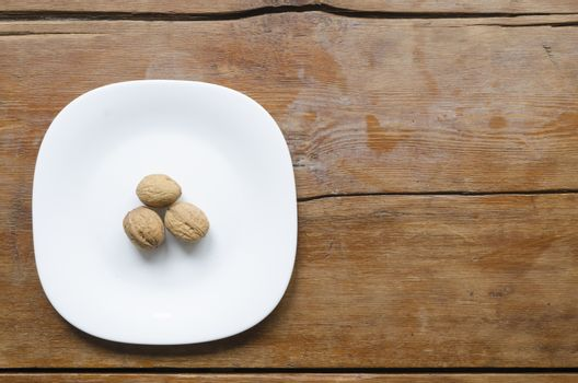 white ceramic dish with three walnuts on the vintage wooden table