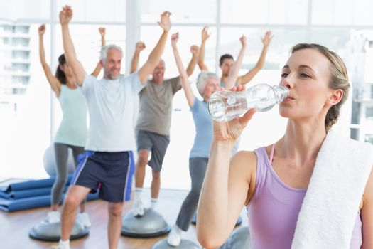 Young woman drinking water with people stretching hands in the background at fitness studio