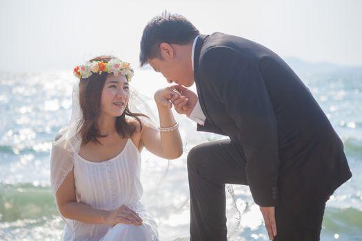 Beautiful asian couple on the beach in wedding dress