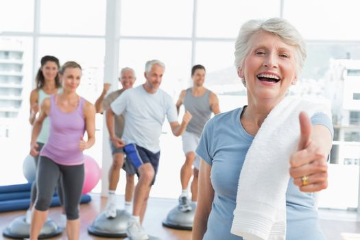Cheerful senior woman gesturing thumbs up with people exercising in the background at fitness studio