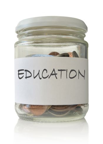 Glass jar filled with coins labeled with education