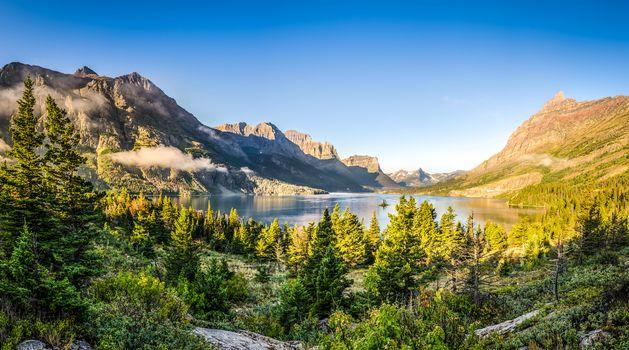 Panoramic landscape view of Glacier NP mountain range and lake, Montana, USA