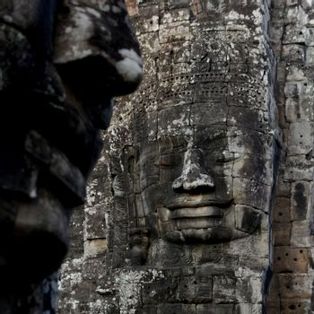 Stone Faces the Tempel Ruin of Angkor Thom in the Temple City of Angkor near the City of Siem Riep in the west of Cambodia.