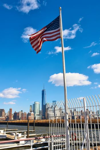 American flag with Manhattan skyline at background