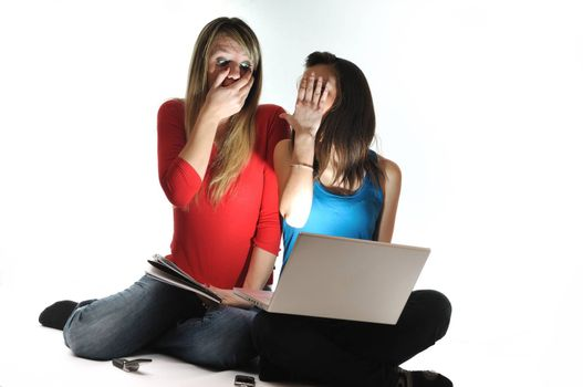 scared and shocked two young woman isolated looking in laptop