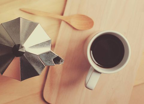 Hot coffee and moka pot with wooden spoon, retro filter effect