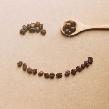 Happy face shaped of coffee beans with wooden spoon, retro filter effect
