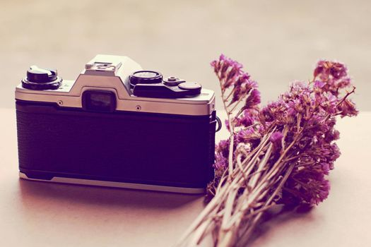 Old camera and bunch of flowers with retro filter effect