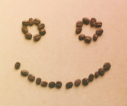 Happy face shaped of coffee beans with retro filter effect