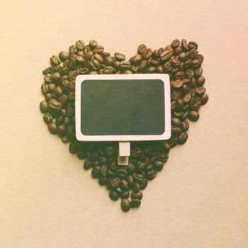 Heart shape from coffee beans with blank blackboard, retro filter effect