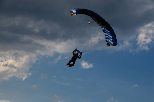 skydiver with blue umbrella on sky