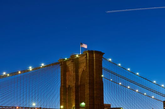 Close up of a pillar of the Brooklyn bridge with flag at night