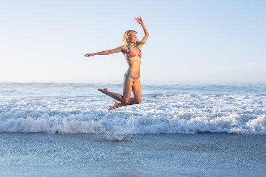 Happy blonde leaping on the beach in bikini
