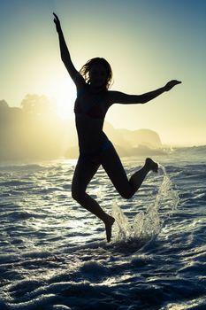 Happy blonde in the sea leaping in bikini