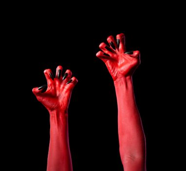 Red devil hands with black nails, Halloween theme, isolated on black background