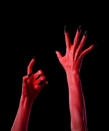 Red spooky devil hands with black nails, Halloween theme, isolated on black background