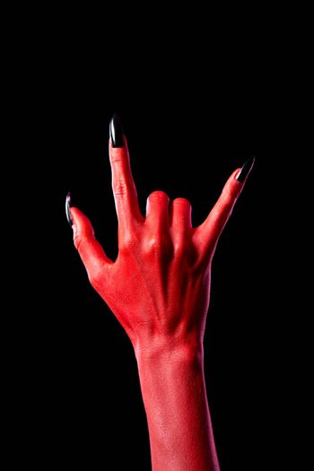 Devil hand showing heavy metal gesture, isolated on black background
