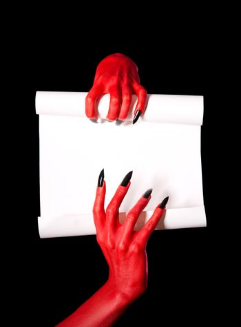 Red devil hands holding blank paper scroll, deal with devil concept for Halloween