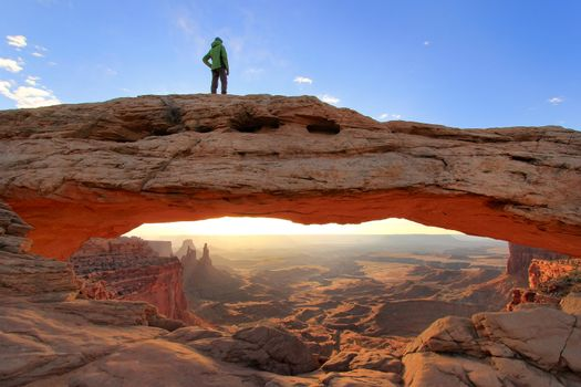Silhouetted person standing on top of Mesa Arch, Canyonlands Nat