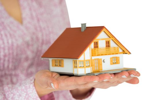 Hands showing a miniature model home