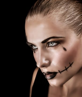 Portrait of aggressive young woman with creepy makeup and black tear isolated on black background, Halloween celebration concept
