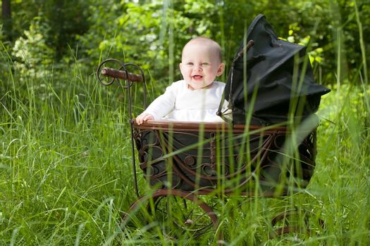 Baby girl is sitting in a vintage pram