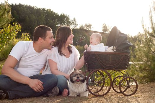 Portrait of parents with their baby girl is sitting in a vintage pram