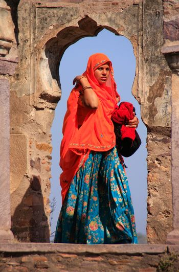 Indian woman in colorful sari standing in the arch, Ranthambore