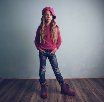 Cute pre-teen girl wearing fashion clothes and shoes posing on wooden floor