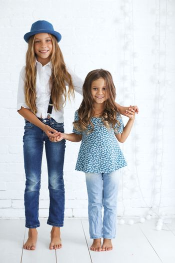 Cute kids 5 and 8 years old wearing trendy blue clothes posing over white brick wall