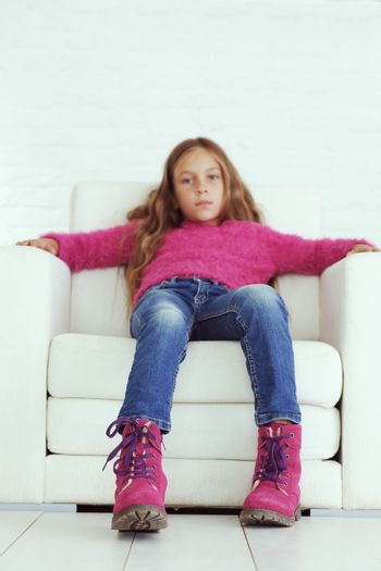 Cute pre-teen girl wearing fashion winter clothes posing in white interior, focus on shoes