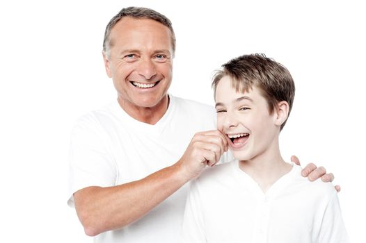 Playful father and son, pinching cheeks