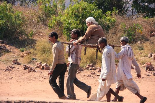 Local men carrying old woman at Ranthambore Fort, India
