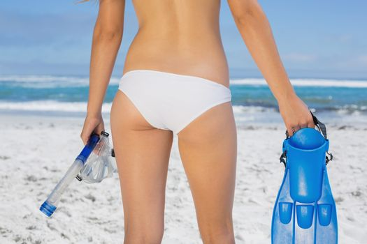 Rear view of fit woman holding fins and snorkel on the beach