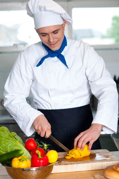 Chef cutting vegetables in kitchen