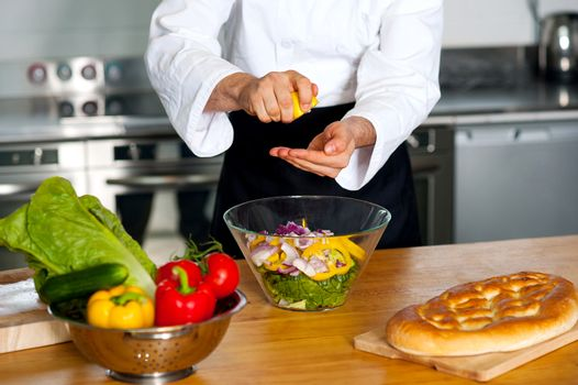 Male chef put ingredient in the glass bowl