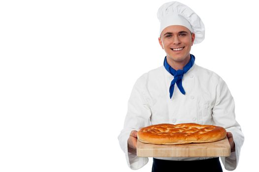 Young baker holds a loaf on breadboard