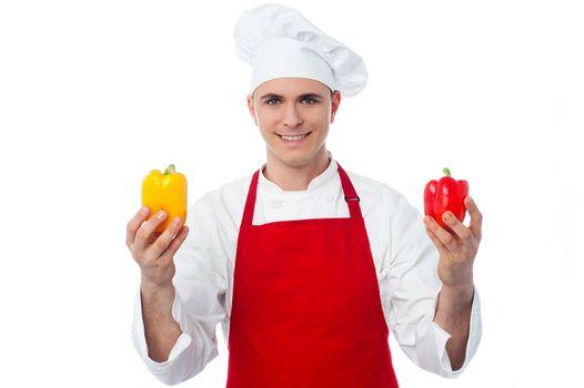 Chef in uniform showing capsicums