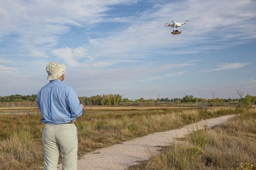 FORT COLLINS, CO, SEPTEMBER 28, 2014:  Photogrpaher, Marek Uliasz, is lflying the DJI Phantom 2 quadcopter drone with Panasonic Lumix GM1 camera on board over a marsh natural area.