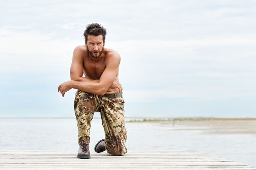 Portrait of a handsome muscular man in camouflage trousers