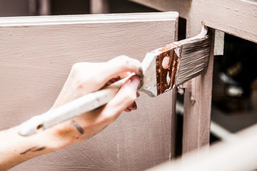 Closeup of Person Painting Kitchen Cabinets